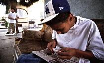 A Hispanic American boy rolling a marijuana joint in  South-Central Los Angeles, USA 2003 - Andrija Ilic - 07-05-2003