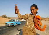 A Berber girl selling argan oil by the roadside. Berber women in Morocco harvest argan nuts from Iron Wood trees for medicinal and culinary use. Argan oil claims many benefits including treatment of h... - Boris Heger - .,2000s,2003,adolescence,adolescent,adolescents,africa,african,africans,agricultural,agriculture,arab,arabs,BENEFIT,benefits,child,Child Labor,child labour,CHILDHOOD,children,crop,crops,developing,EBF