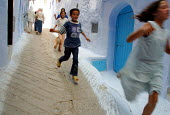 Moroccan children running through the winding streets of Chef Chaouen, a village in the Rif area of Morocco. Morocco 2004 - Boris Heger - 01-09-2004