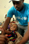 A UNICEF aid worker at a feeding centre for malnourished children in Eastern Ethiopia. The children receive high protein supplements to assist in their recovery. Ethiopia 2005 - Boris Heger - 06-09-2005