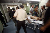Shifa Hospital. Gaza City. A man badly injured by an Israeli tank shell is rushed through to the emergency room, in the hospital which is struggling to cope with the mounting injured brought every day... - Thomas Morley - 27-07-2006