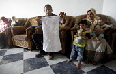 Central Gaza Strip. Mr Ahmed Abdiljawad sits with some of his family and shows of one of the tops he used to make. His textile factory was destroyed by Israeli tanks during a military operation inside... - Thomas Morley - 27-07-2006