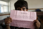 A young Palestinian boy, shows a leaflet dropped by the Israeli military ordering everyone to leave their homes before they start bombing the area, from the shelter of a classroom in a school in Jabal... - Thomas Morley - 29-07-2006