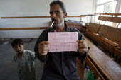 A Palestinian man, shows a leaflet dropped by the Israeli military ordering everyone to leave their homes before they start bombing the area, from the shelter of a classroom in a school in Jabalya ref... - Thomas Morley - 29-07-2006