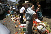 Jewish Market, Haifa, Israel. In the rush for safety as another air raid siern sounds, a market stall is upset and vegetables spill across the road, many of the shoppers stop to help themselves for fr... - Thomas Morley - 21-07-2006