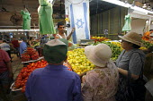 Jewish Market, Haifa, Israel. A Palestinian stall owner in the Jewish market in Haifa shows three of his Jewish customers and the Israeli flag that he hangs from his stall. - Thomas Morley - 21-07-2006