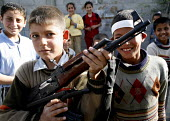 A Palestinian boy in Gaza given an AK 47 to hold by a soldier in the Al-Aqsa brigade. Gaza. 2006 - Thomas Morley - 08-04-2006