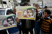 Palestinian children in the streets of Behit Laya hold up posters of Hadil an eight year old girl who died when Israeli rocket fire hit their home destroying it and injuring many other members of the... - Thomas Morley - 23-04-2006