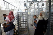 Palestinian family held at the Eretz check point to control the flow of people and goods in and out of Gaza to Israel. The check point is bomb proof and the Israelis issue orders through loud speakers... - Thomas Morley - 23-04-2006