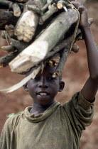 Rwandan refugee child carrying firewood after arrival at Benaco camp, Tanzania. 1994 - Howard Davies - 03-05-1994