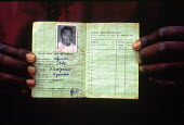 Rwandan refugee with ID card showing ethnicity. The cards were used by Hutu extremists to identify Tutsis during the genocide. Benaco camp, Tanzania. 1994 - Howard Davies - 03-05-1994