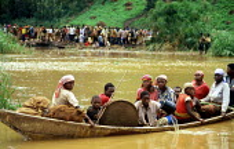 Rwandan refugees crossing the Rusumo river by boat to reach Tanzania. 1994 - Howard Davies - 03-05-1994