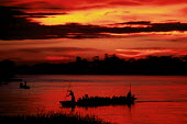 Pirogue with passengers crossing the Congo river at sunset, Kisangani, Zaire - Congo. 1997 - Howard Davies - 03-05-1997