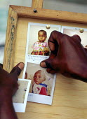 Photographs of unaccompanied Rwandan Hutu refugee children in care of SCF are posted on a notice board.. SCF centre, Goma, Zaire. 1996 - Howard Davies - 03-05-1996
