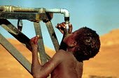 Somali children collecting clean water from an Oxfam tapstand, Bardere, Somalia. 1993 The provision of clean drinking water prevents water borne disease. - Howard Davies - 03-05-1993