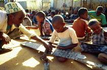 Teacher with pupils at Koran school, Bardere, Somalia. 1993 - Howard Davies - 03-05-1993
