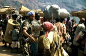 Ethiopian UN soldier assisting Rwandan refugees, crossing into Zaire from Rwanda. Bukavu, 1994. - Howard Davies - 1990s,1994,africa,african africans,agencies,aid agency,aid worker,arm arms,army,assist assisting,assistance,Asylum Seeker,Asylum Seeker,bag bags,bed,bedding,beds,Beret,berets,Blue,border,border border