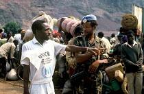 UNHCR aid worker with an Ethiopian UN soldier, assisting Rwandan refugees crossing into Zaire from Rwanda. Bukavu, 1994. - Howard Davies - 1990s,1994,africa,african africans,agencies,aid agency,aid worker,arm arms,army,assist assisting,assistance,Asylum Seeker,Asylum Seeker,bag bags,Beret,berets,bib bibs,Blue,border,border borders,border