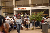 Queues outside mobile phone company Orange, to take advantage of a local promotion. - Howard Davies - africans,2000s,2006,africa,african,africans,botswana,Botswanan,bought,brand,brands,buy,buyer,buyers,buying,campaign,CAMPAIGNING,campaigns,CAPITALISM,capitalist,cell,cellular,cities,city,commodities,co