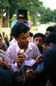 Community worker from a local NGO distributing discounted condoms. Orissa, India. 1997 - Howard Davies - .,1990s,1997,Acquired immune,adult,adults,aid workers,AIDS,asia,asian,asians,communities,Community,con,condom,condoms,contraception,contraceptive,contraceptives,deficiency syndrome,developing,DISEASE,