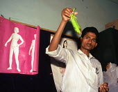 Community worker showing correct condom use at a sex education class for street children, a project funded by DFID. Calcutta, India. 1997 - Howard Davies - 1990s,1997,Acquired immune,AIDS,Asia,asian,asians,CHILD,CHILDHOOD,children,communities,Community,condom condoms,contraception,contraceptive,CONTRACEPTIVES,contraceptivestraceptives,deficiency syndrome