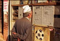 Nepalese reading communal newspapers posted on wall. Kathmandu Nepal. 1997 - Howard Davies - 03-05-1997