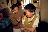 Tibetan refugee receiving a vaccination at a halfway house having walked from Tibet across the Himalayas to escape Chinese occupied Tibet. Kathmandu, Nepal. 1997 - Howard Davies - 03-05-1997