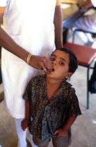 Tamil refugee child having polio immunisation, having returned home having been a refugee in India. Mannar Island reception centre, Sri Lanka. 1995 - Howard Davies - 03-05-1995
