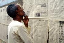 Bangladeshi man reading communal newspaper. Dhaka, Bangladesh. 1992 - Howard Davies - 03-05-1992