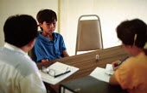 Unaccompanied refugee child being interviewed by UNHCR before return to Vietnam. Marang transit camp, Malaysia. 1992 - Howard Davies - 03-05-1992