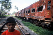 A boy stands by the wreckage of the Colombo - Galle train which was struck by the Tsunami with around 1500 people losing their lives, Sri Lanka 2005 - Howard Davies - 05-03-2005