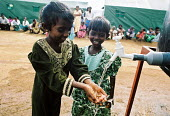 Displaced children survivors of the Tsunami disaster collect clean drinking water provided by Oxfam in IDP camps to the north of Batticaloa on the east coast of Sri Lanka. The provision of hygiene kit... - Howard Davies - 05-03-2005