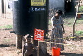 Locals collect water form an Oxfam tapstand close to markers indicating presence of landmines and ordnance distributed around a village to the north of Batticaloa. The Tsunami destroyed a nearby army... - Howard Davies - 05-03-2005