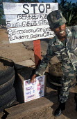 A governemnt soldier shows a poster warning about landmines, many of which were distributed when the nearby army camp to the north of Batticaloa was struck by the Tsunami. Sri Lanka 2005 - Howard Davies - 05-03-2005