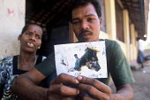 A man with his wife close by holds a photograph showing his children, three of whom were lost when the Tsunami struck their village in eastern Sri Lanka. They are living in a camp for families displac... - Howard Davies - 2000s,2005,adult,adults,asia,asian,camp,camps,CHILD,CHILDHOOD,children,developing,DIA,disaster,disasters,displaced,displacement,earthquake,earthquakes,environment,FAMILY,FEMALE,I,idp,idps,incident,inc