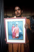 A Tamil woman in a displaced peoples camp holds a photograph of the two children she lost in the Tsunami. Batticaloa district, Sri Lanka. 2005 - Howard Davies - 05-03-2005