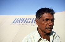 A Tamil man who lost his wife in the Tsunami outside his temporary UNHCR shelter, Navaldi, Batticaloa, Sri Lanka 2005 - Howard Davies - 05-03-2005