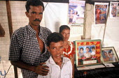 A Tamil family in a displaced peoples camp with a photograph of the three children they lost in the Tsunami. Jaffna district, Sri Lanka. 2005 - Howard Davies - 05-03-2005