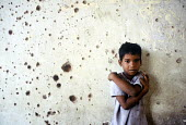 A child living with her family having been displaced by the civil war in the damaged remains of Jaffna railway station, Jaffna, Sri Lanka 2005 - Howard Davies - 2000s,2005,asia,asian,boy,boys,bullet,Bullets,child,CHILDHOOD,children,Civil War,conflict,conflicts,damaged,displaced,displacement,families,family,holes,I,idp,idps,internally,Internally Displaced Pers