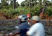 A motorbike passes a sign for a landmine field in northern Sri Lanka where hundreds of thousands of landmines and ordnance litter the countryside. Jaffna district, Sri Lanka 2005 - Howard Davies - 2000s,2005,ACE,armed forces,asia,asian,BOMB,bombing,bombings,BOMBS,communicating,communication,conflict,conflicts,culture,danger,DANGEROUS,DIA,displaced,displacement,earthquake,earthquakes,hazard,haza