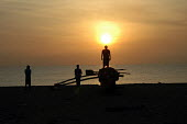 On the six month anniversary of the Tsunami disaster Sri Lankan fishermen watch the dawn rise over Navaladi beach where more than 700 people lost their lives during the Tsunami. Batticaloa, Sri Lanka... - Howard Davies - 05-03-2005