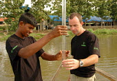Oxfam water technicians check the turbidity of water which has been filtered at an Oxfam water treatment plant for people displaced by the tsunami. Ampara, Sri Lanka 2005 The provision of clean drinki... - Howard Davies - 05-03-2005