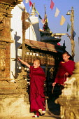 Buddhist monks with prayer wheels. At the Swayambhunath stupa, in Kathmandu. - Howard Davies - 1990s,1997,ACE,ace arts culture,adolescence,adolescent,adolescents,architecture,arts,asia,asian,asians,attraction,attractions,Bhikkhu,Bhikkhunis,Bhikkhus,Bhiksu,blow,blowing,boy,boys,buddha,buddhism,B