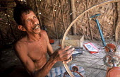 A man who has received a cash grant from Oxfam following the tsunami to restart his bicycle repair business. Batticaloa district, Sri Lanka 2005 - Howard Davies - 03-11-2005