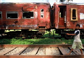 A boy walks along the newly repaired tracks past the damaged Galle - Colombo train which was hit by the Tsunami with the loss of 1500 passengers. Sri Lanka 2005 - Howard Davies - 03-11-2005