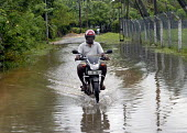 A motorcyclist riding a flooded road on the south coast of Sri Lanka caused by the monsoon. 2007 - Howard Davies - 21-10-2007