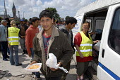 Volunteers from local aid agency La Belle Etolie make a food distribution in a car park to asylum seekers camped in sand dunes near the port of Calais on the north coast of France. 2009 - Howard Davies - 15-07-2009