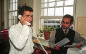An asylum seeker receives assistance from an advice worker using a phone interpreter service at the Welsh Refugee Council, Swansea, Wales, UK 2002 - Howard Davies - 2000s,2002,advice,ADVISE,agencies,agency,aid,aid workers,assistance,Asylum Seekers,Asylum Seekers,BAME,BAMEs,bilingual,Black,BME,bmes,britain,charitable,charities,charity,communicating,communication,C