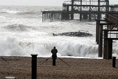 A man watching waves by the ruins of the West Pier during a winter storm. Brighton UK 2008 - Howard Davies - 10-03-2008