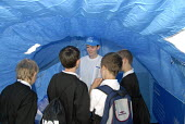 A volunteer speaks with pupils in refugee tents set up by UNHCR in Trafalgar Square to commemorate World Refugee Day, London - Howard Davies - 2000s,2008,activist,activists,aid agency,assistance,camp,CAMPAIGN,campaigner,campaigners,CAMPAIGNING,CAMPAIGNS,camps,child,CHILDHOOD,children,communicating,communication,conversation,conversations,day